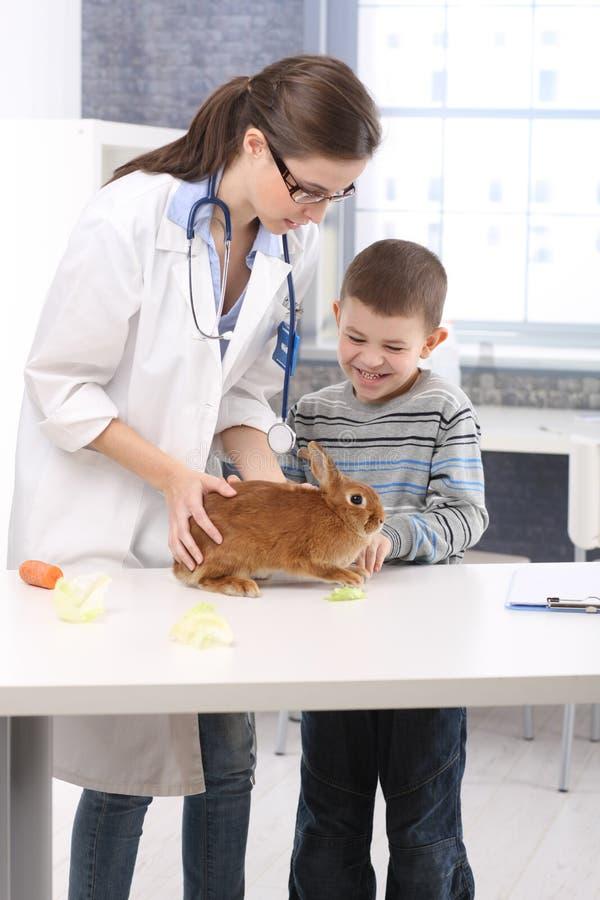 Cabrito feliz en el veterinario con el conejo fotos de archivo