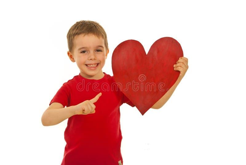 Cabrito feliz que señala a la dimensión de una variable del corazón foto de archivo