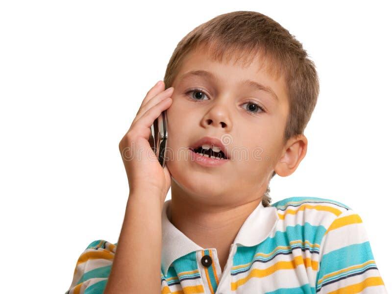 Cabrito serio que habla sobre el teléfono foto de archivo