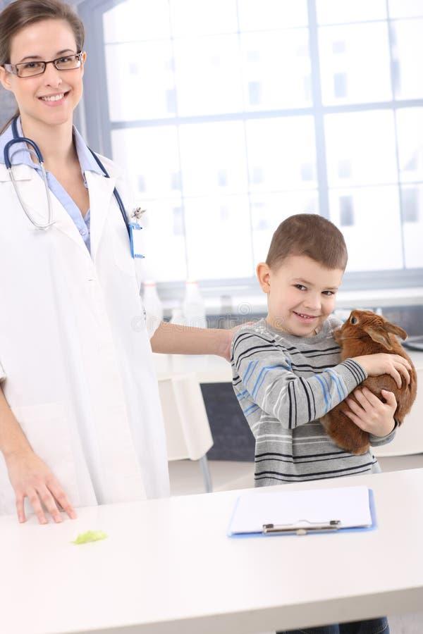 Cabrito sonriente con el conejo del animal doméstico en el veterinario fotografía de archivo libre de regalías