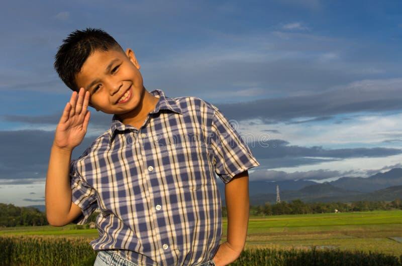 Cabrito sonriente con un saludo de mano foto de archivo libre de regalías