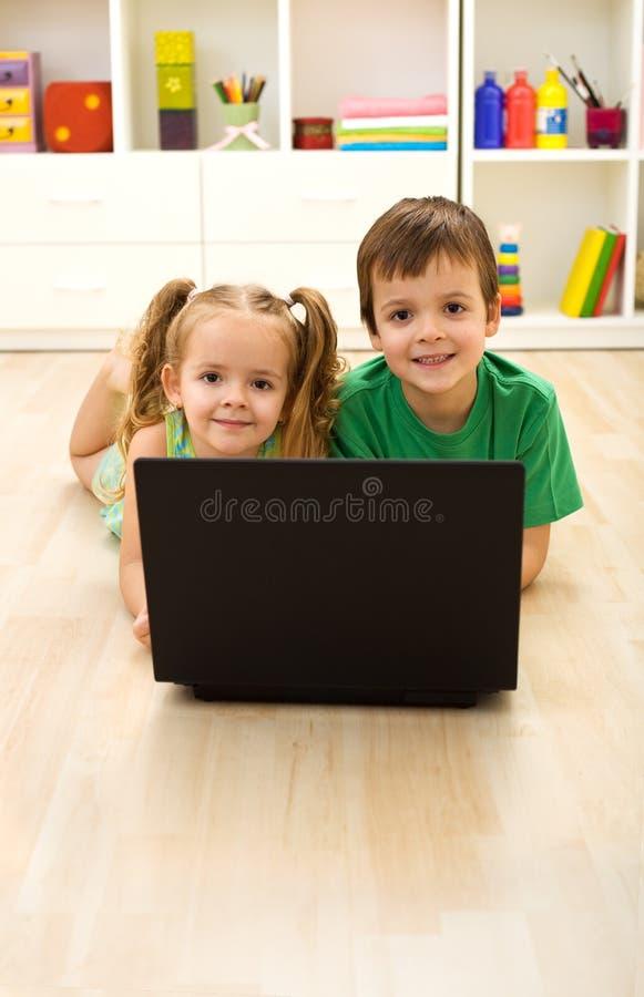 Cabritos con la computadora portátil que pone en el suelo en el país imagen de archivo libre de regalías