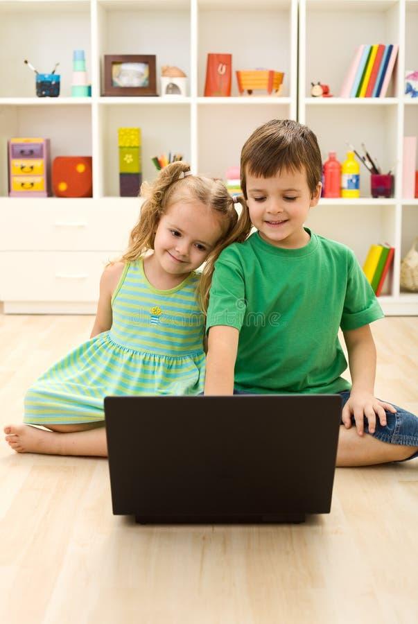 Cabritos con la computadora portátil, sentándose en el suelo foto de archivo libre de regalías