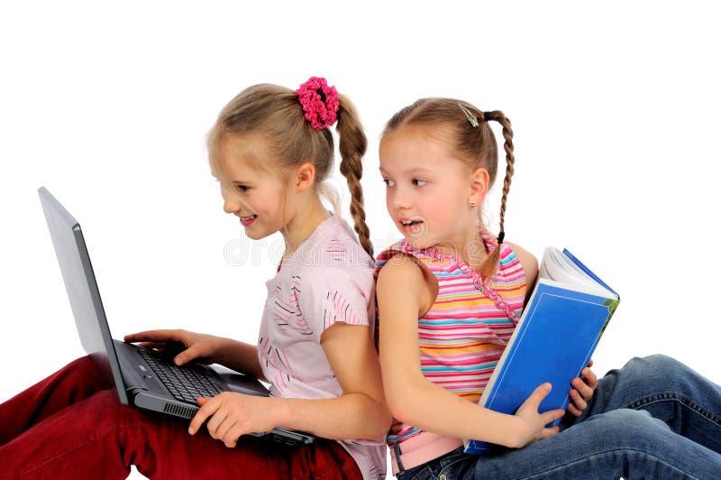 Cabritos con la computadora portátil y el libro imagen de archivo