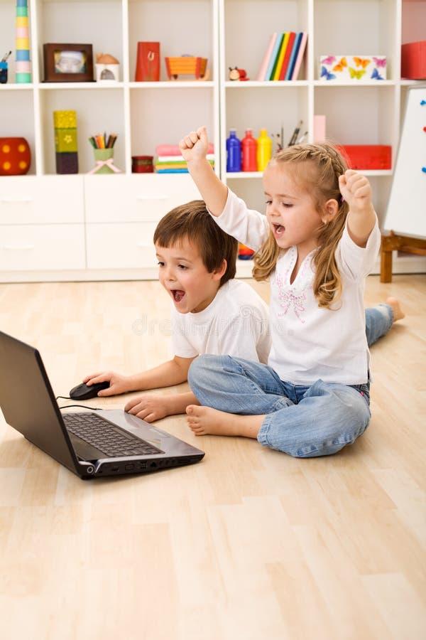 Cabritos emocionados alrededor para ganar el juego de ordenador imagen de archivo libre de regalías