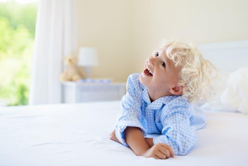 Cabritos en cama Niños en pijamas Dormitorio de la familia fotografía de archivo