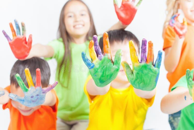 Cabritos felices con las manos pintadas El día de los niños internacionales fotografía de archivo