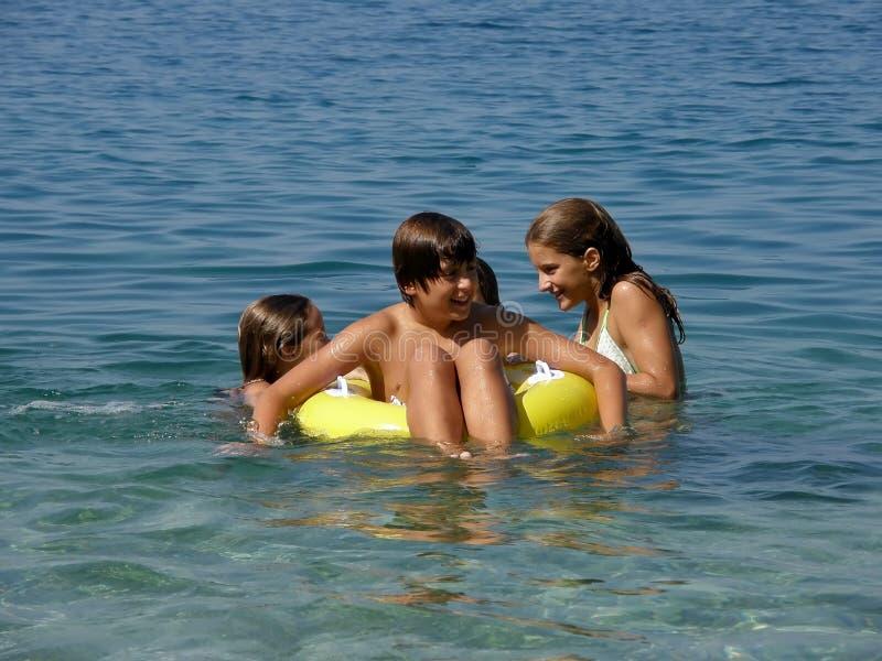 Cabritos felices con los juguetes de la playa en el mar foto de archivo libre de regalías
