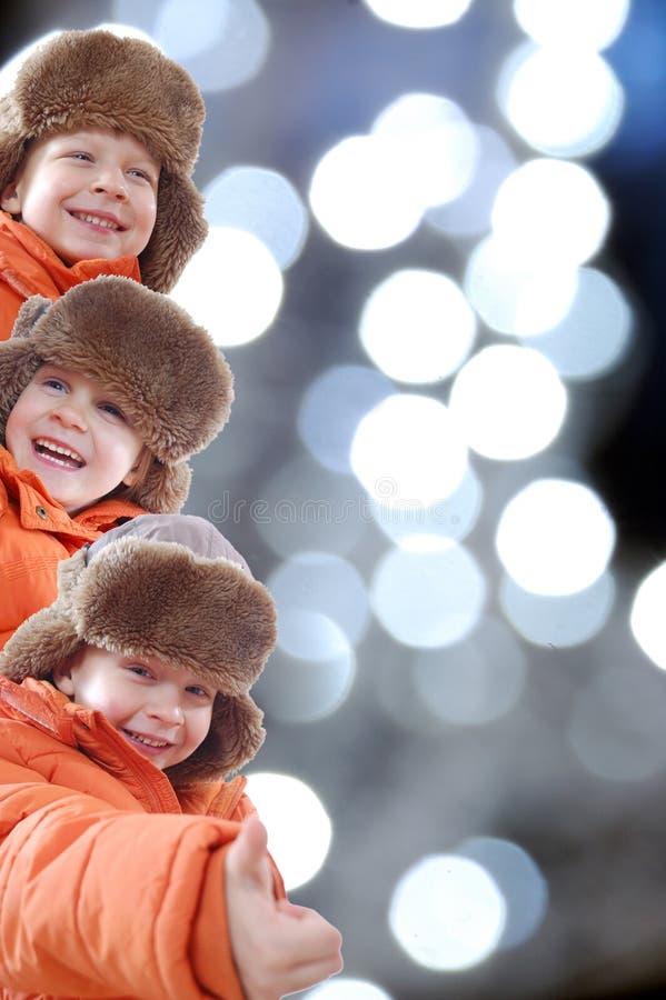 Cabritos felices del invierno contra luces coloridas fotos de archivo