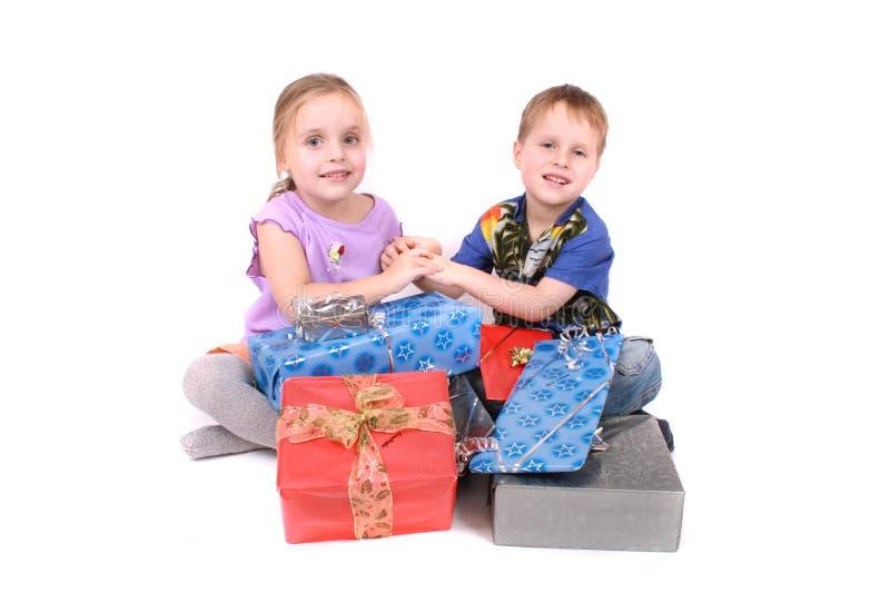 Cabritos felices jovenes con los presentes foto de archivo