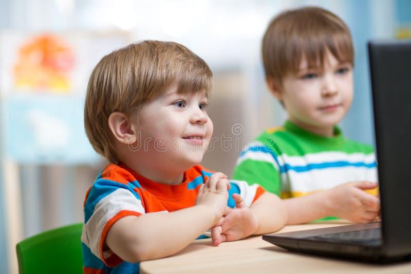 Cabritos felices que miran la computadora portátil foto de archivo libre de regalías