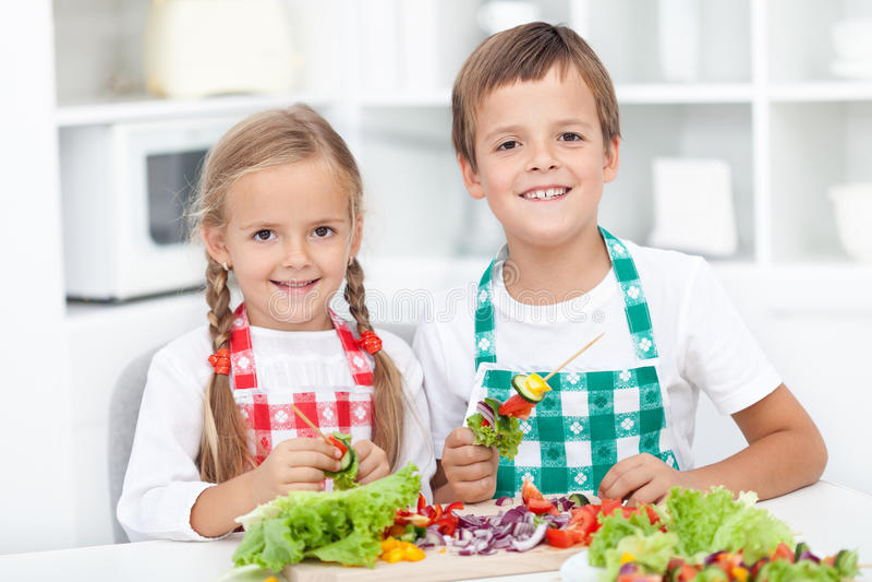 Cabritos felices que preparan una comida en la cocina fotos de archivo