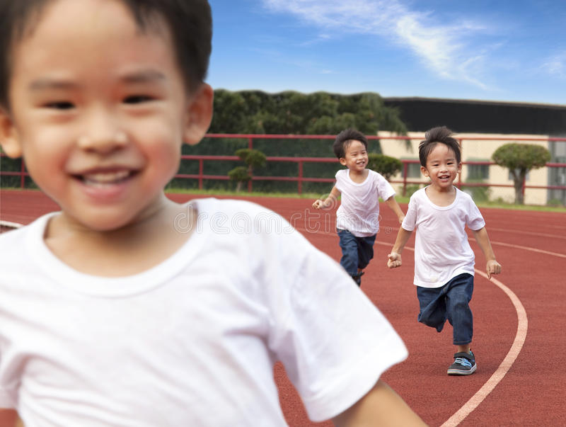Cabritos felices que se ejecutan en la pista del estadio fotos de archivo