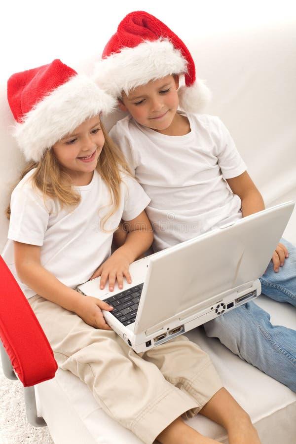 Cabritos que buscan por regalos de Navidad en línea imágenes de archivo libres de regalías