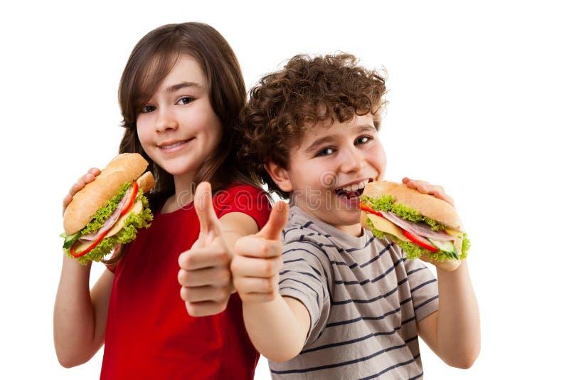Cabritos que comen los emparedados sanos imagenes de archivo