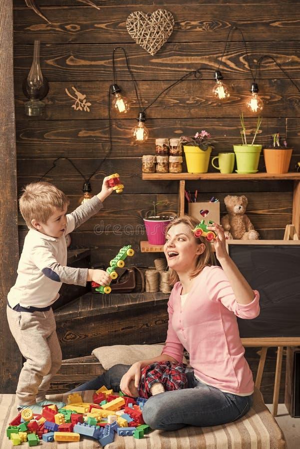 Cabritos que juegan con los juguetes Concepto educativo del juego El profesor de la mamá o del cuarto de niños y el muchacho rubi imagenes de archivo