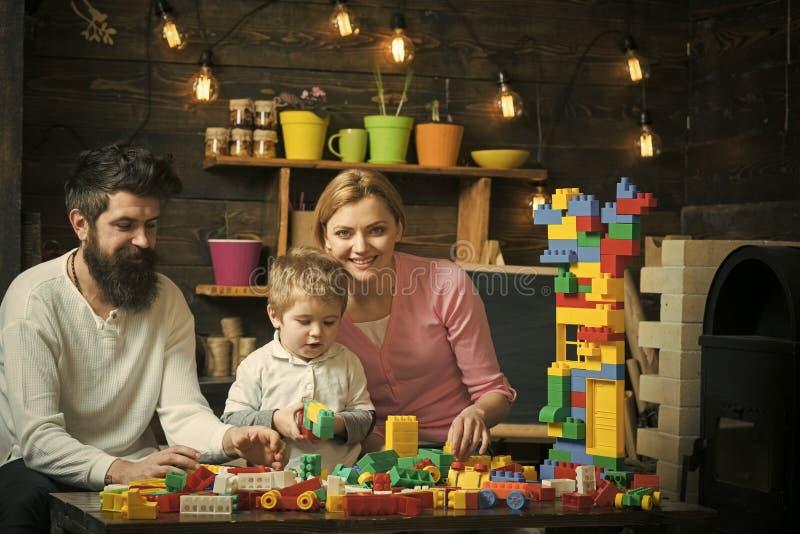 Cabritos que juegan con los juguetes Familia que disfruta del tiempo junto Papá e hijo que juegan con los bloques plásticos Padre fotografía de archivo libre de regalías