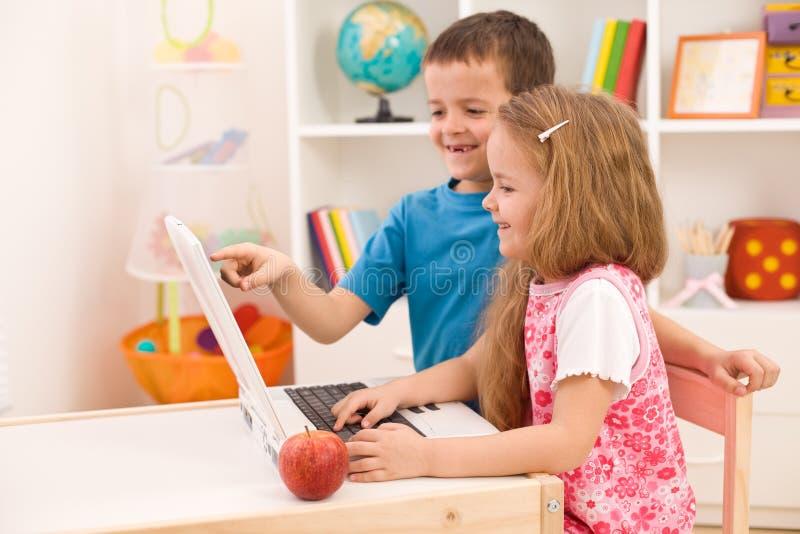 Cabritos que juegan en el ordenador portátil en el país imagen de archivo libre de regalías