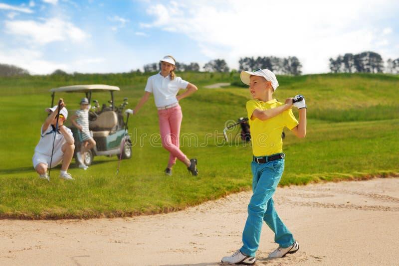 Cabritos que juegan a golf fotos de archivo