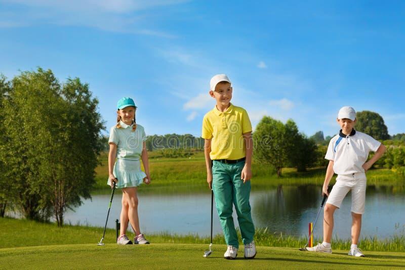 Cabritos que juegan a golf foto de archivo libre de regalías