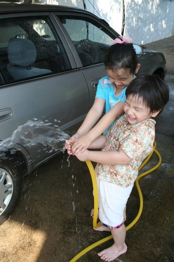 Cabritos que lavan el coche foto de archivo
