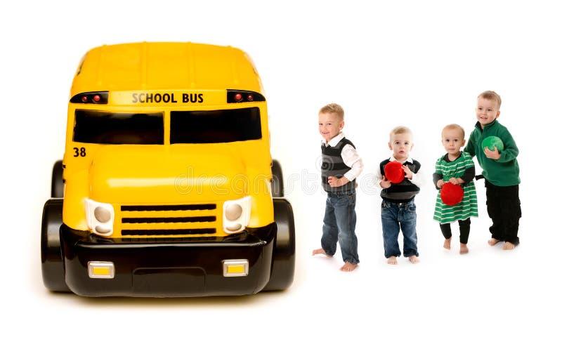 Cabritos que suben al autobús escolar imagen de archivo libre de regalías