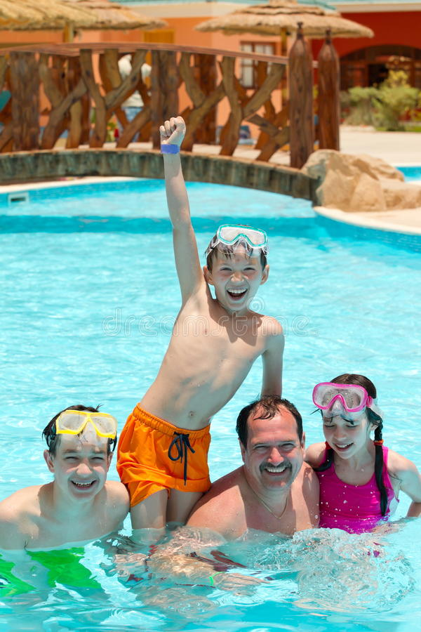 Cabritos y padre en piscina imagen de archivo