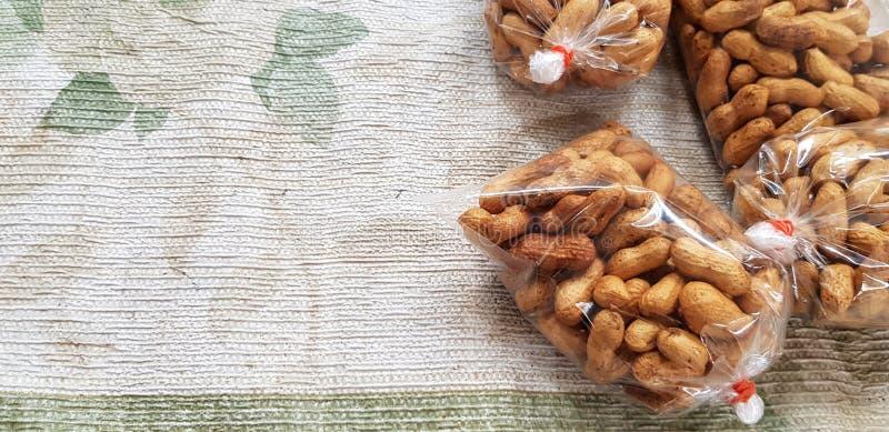 Cacahuetes asados en la bolsa de plástico en venta en algodón viejo en el mercado local de la comida de la calle fotografía de archivo libre de regalías