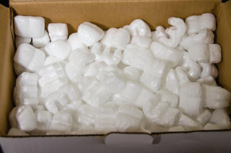 Cacahuetes de la espuma de poliestireno en un envase de la cartulina imagenes de archivo