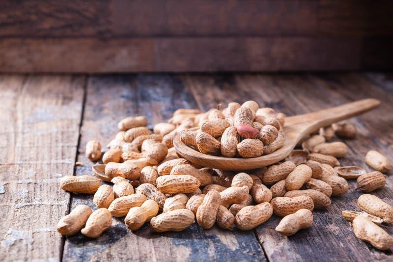 Cacahuetes en cáscara en piso de madera imagenes de archivo