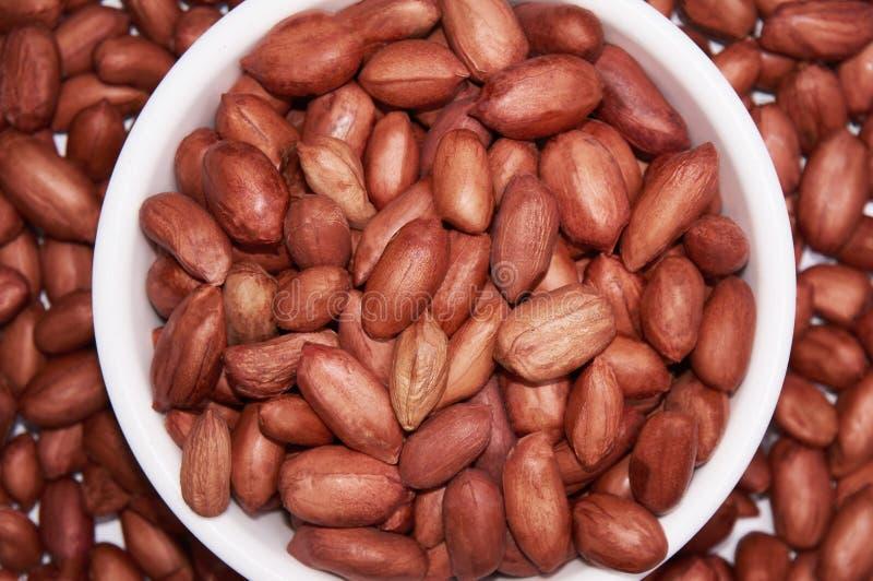 Cacahuetes en un cuenco blanco en un fondo de cacahuetes Fondo del alimento fotografía de archivo libre de regalías