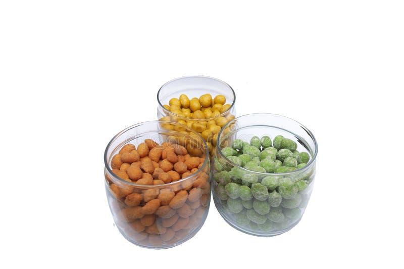 Cacahuetes multicolores en una corteza curruscante en tres tarros de cristal fotografía de archivo