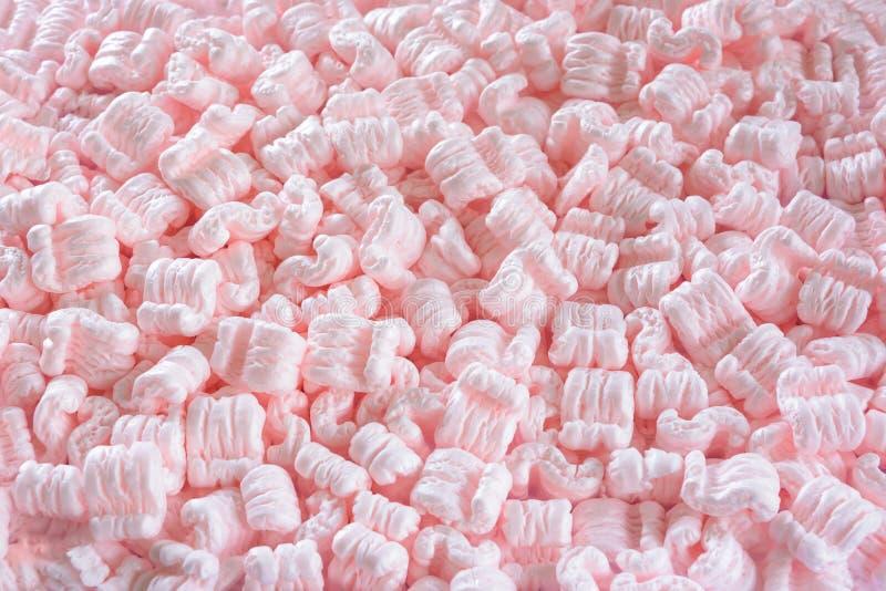 cacahuetes rosados S-formados del embalaje como fondo fotografía de archivo
