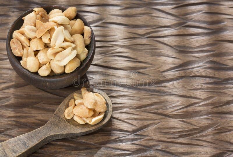 Cacahuetes tostados en el fondo de madera - hypogaea del cacahuete imagen de archivo libre de regalías