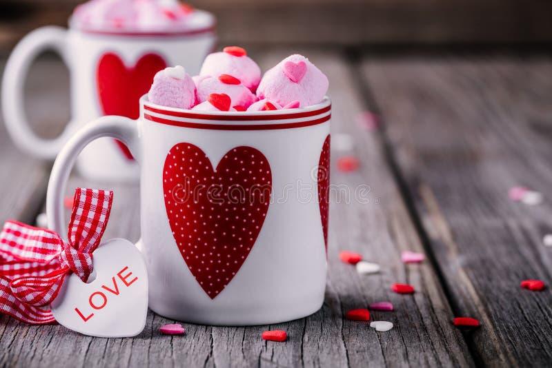 Cacao caliente con la melcocha rosada en tazas con los corazones para el día de San Valentín fotos de archivo libres de regalías