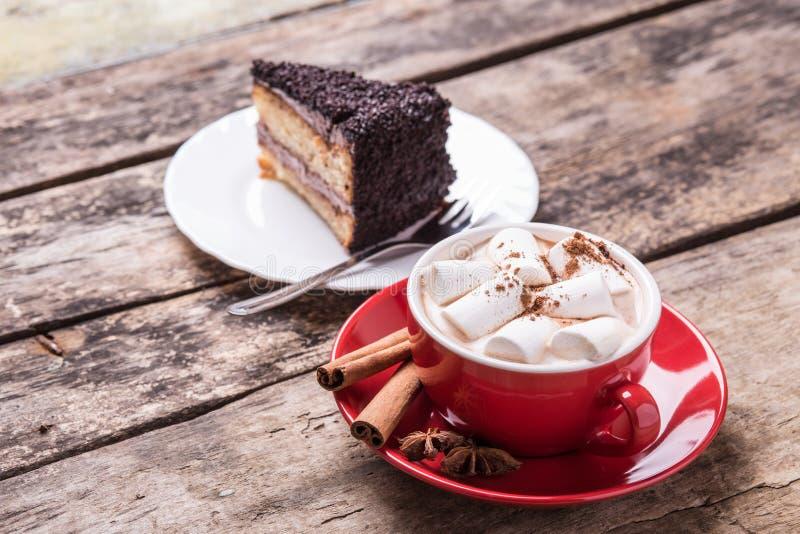 Cacao caliente con las melcochas y la rebanada de torta imagen de archivo