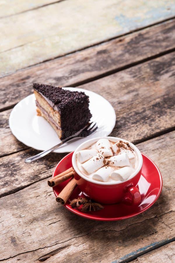 Cacao caliente con las melcochas y la rebanada de torta fotos de archivo