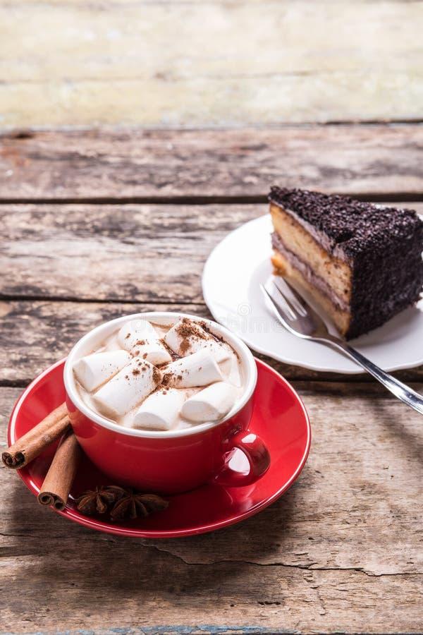 Cacao caliente con las melcochas y la rebanada de torta fotografía de archivo libre de regalías