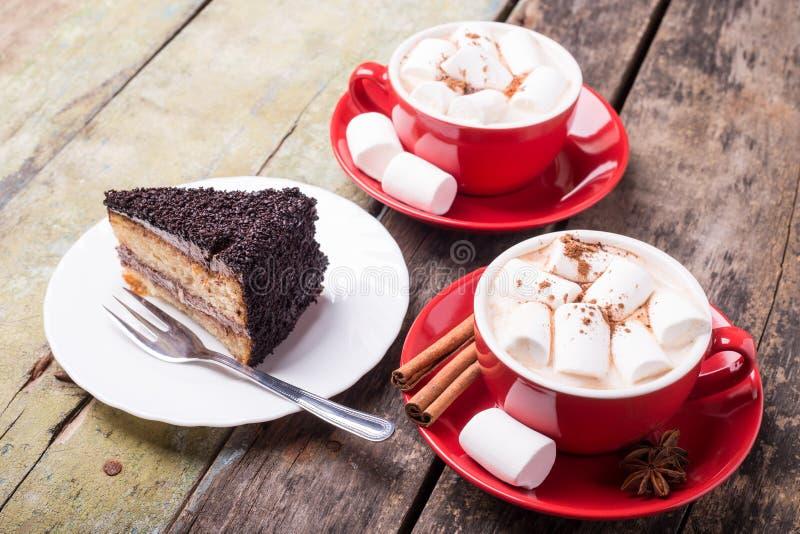 Cacao caliente con las melcochas y la rebanada de torta fotos de archivo libres de regalías