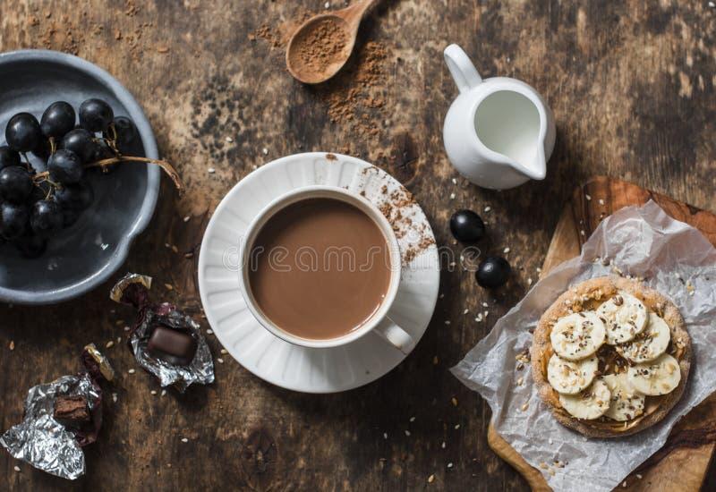 Cacao, cracker met pindakaas, banaan, vlas en chiazaad, druiven - snack, ontbijtlijst Comfortabel atmosfeerontbijt op hout stock foto