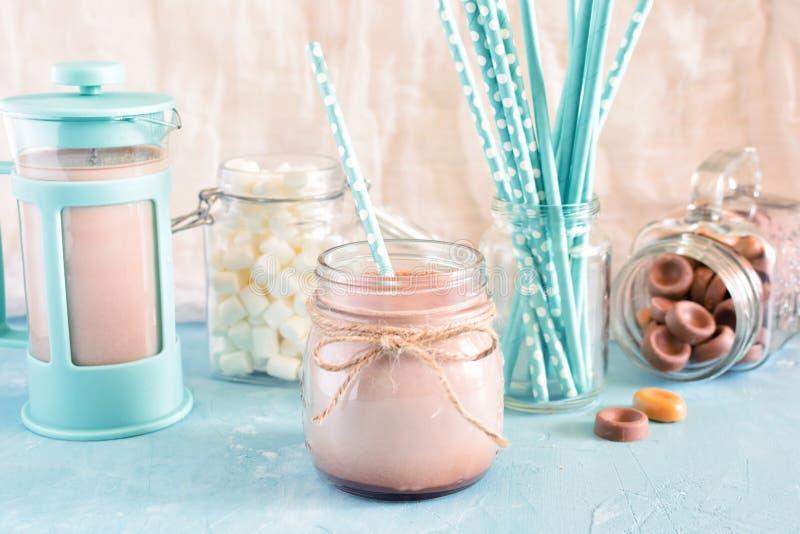 Cacao dans un pot de paille Dans le fond, un pot bleu de café, des guimauves et des tubes de cocktail de turquoise dans une tache photographie stock
