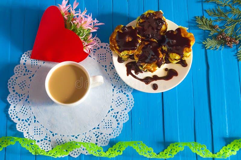 Cacao de la bebida de la mañana con las crepes y las flores deliciosas en el h fotos de archivo libres de regalías