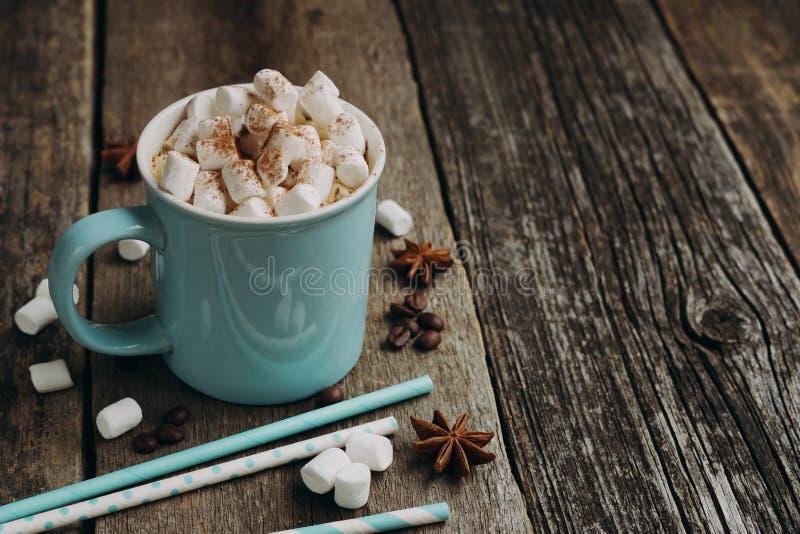 Cacao en una taza azul con las melcochas imagen de archivo