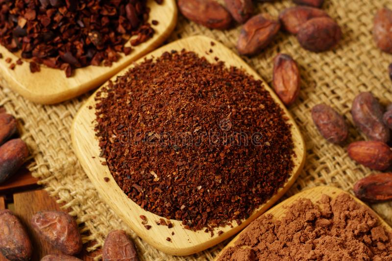 Cacao nibs, cacao powder and cocoa beans on burlap. Background royalty free stock images