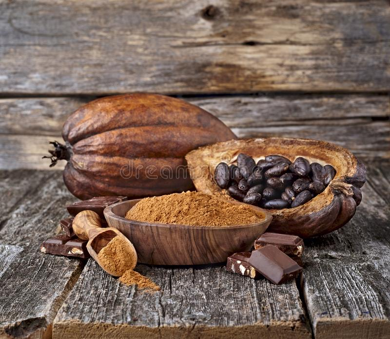 Cacao powder with cocoa beans and chocolate. Rustic style stock photography