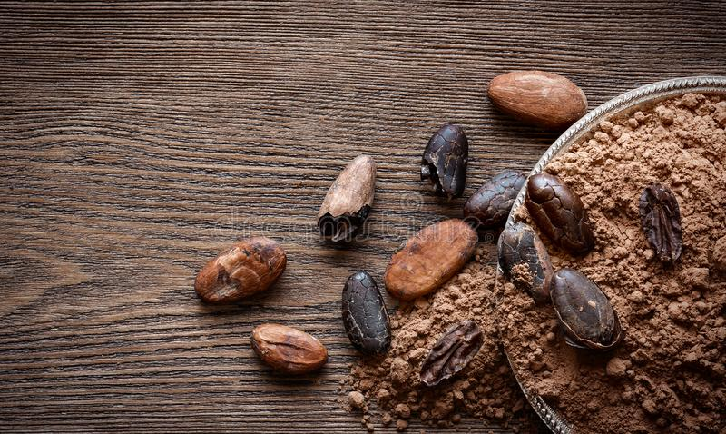 Cacao powder and cocoa beans on wooden background. Cacao powder and cocoa beans on dark wooden background royalty free stock photography
