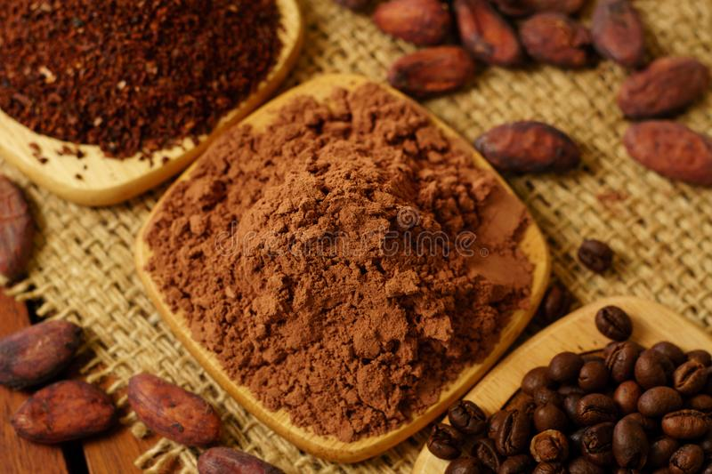 Cacao powder, cocoa nibs, and coffee beans on wooden plates on burlap. Background stock images