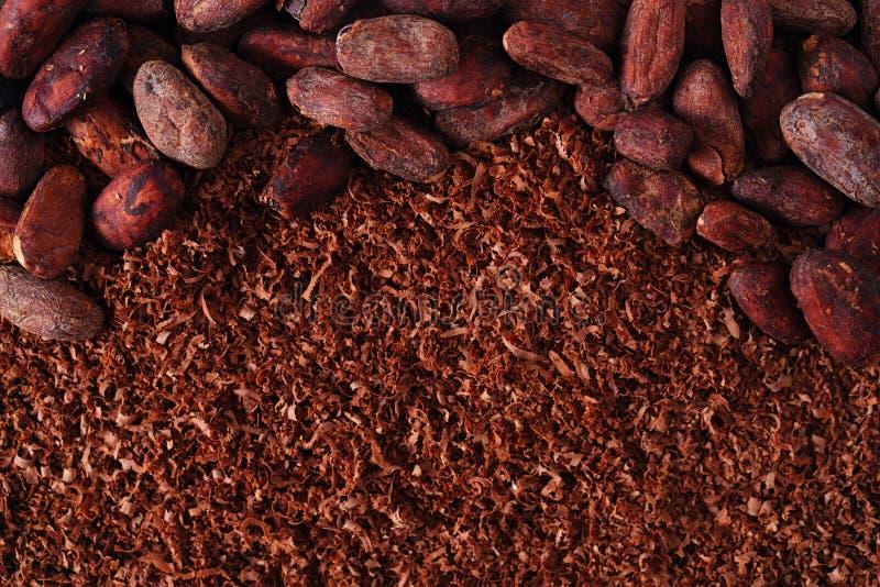 Cacaobonen en geraspte chocoladeachtergrond stock afbeeldingen