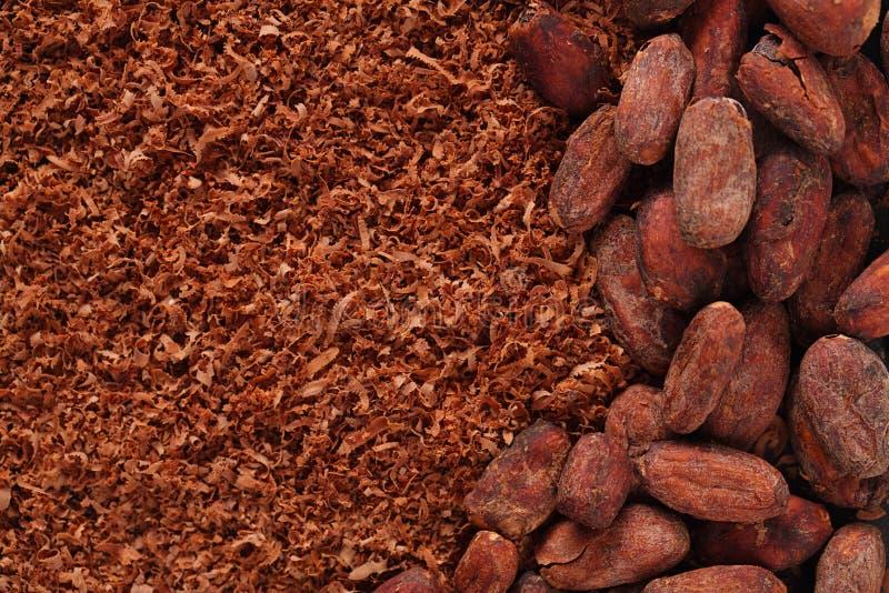 Cacaobonen en geraspte chocoladeachtergrond stock fotografie
