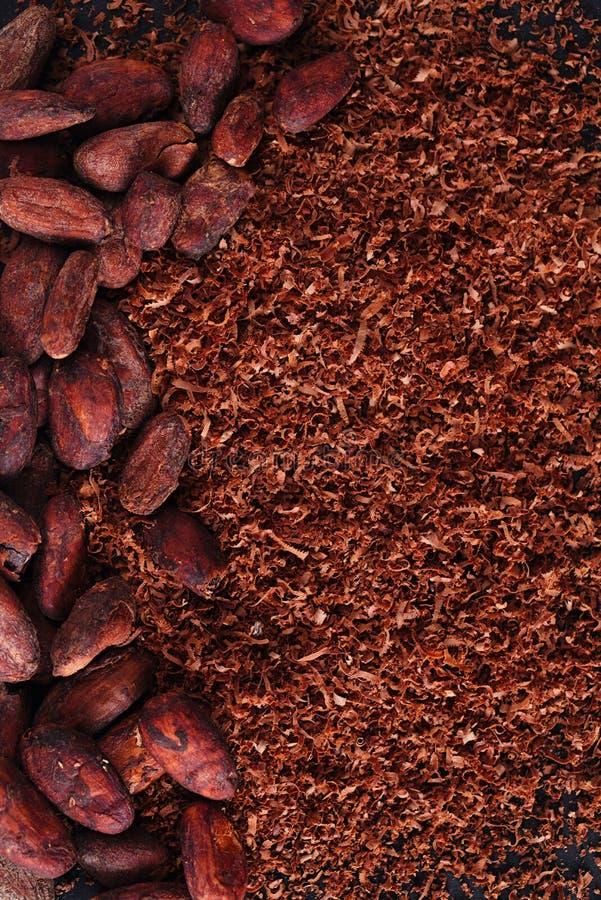 Cacaobonen en geraspte chocoladeachtergrond op zwarte stock foto's